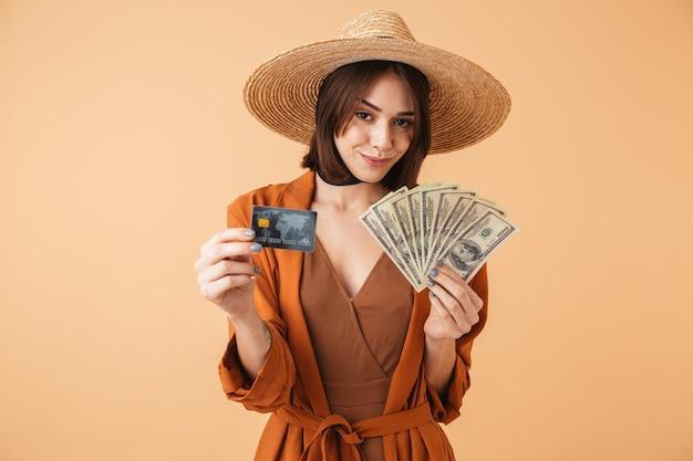 Piękna młoda kobieta w słomkowym kapeluszu i letnim stroju stojąca na białym tle nad beżową ścianą, trzymająca kartę kredytową palstic, pokazującą banknoty pieniędzy