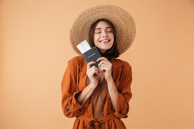 Piękna młoda kobieta w słomkowym kapeluszu i letnim stroju stojąca na białym tle nad beżową ścianą, trzymająca paszport z biletami lotniczymi