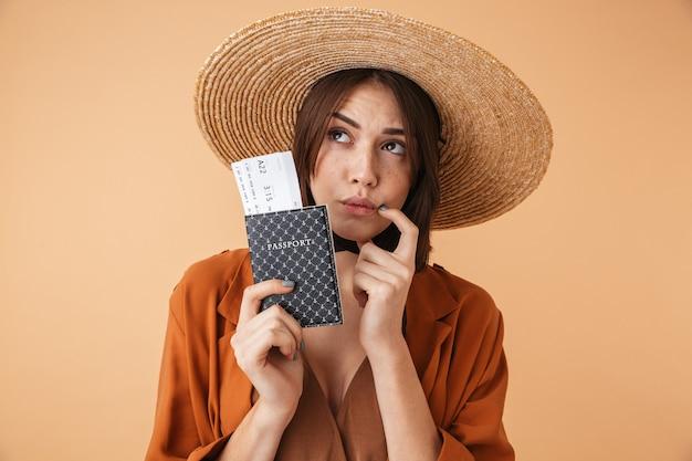 Piękna młoda kobieta w słomkowym kapeluszu stojąca na białym tle nad beżową ścianą, pokazująca paszport z biletami lotniczymi