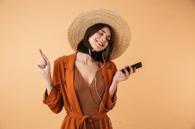 Piękna młoda kobieta w słomkowym kapeluszu stojąca na białym tle nad beżową ścianą, słuchająca muzyki przez słuchawki, trzymająca telefon komórkowy