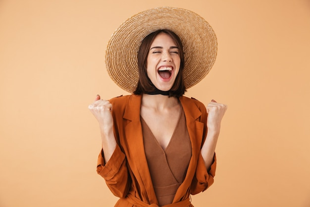 Piękna młoda kobieta w słomkowym kapeluszu stojąca na białym tle nad beżową ścianą, świętująca sukces