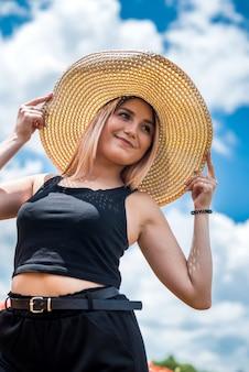 Piękna młoda kobieta w słomkowym kapeluszu w polu maku w okresie letnim. piękna natura