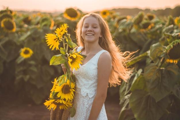 Piękna młoda kobieta w słonecznikowym polu. portret młodej kobiety w słońcu. koncepcja alergii na pyłki. szczęście w stylu życia na świeżym powietrzu