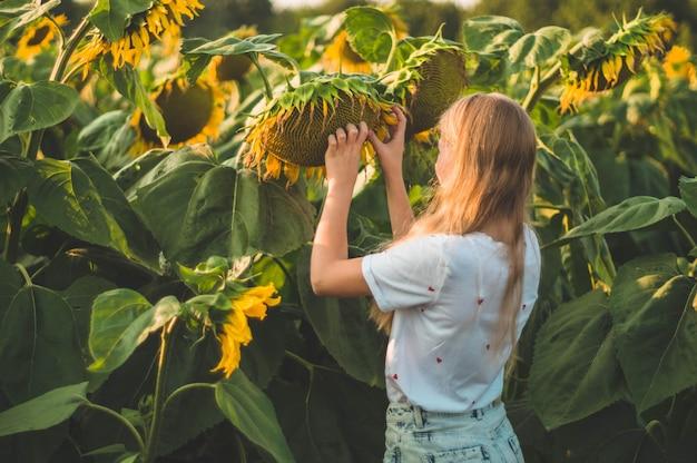 Piękna młoda kobieta w słonecznikowym polu. portret młodej kobiety w słońcu. koncepcja alergii na pyłki