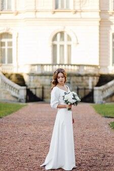 Piękna młoda kobieta w ślubnej sukni pozuje na ulicie w mieście