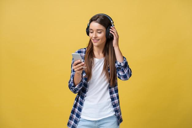 Piękna młoda kobieta w słuchawkach, słuchając muzyki i śpiewając na żółtym tle.