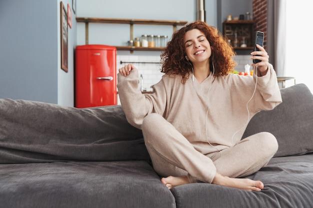 Piękna młoda kobieta w słuchawkach, słuchając muzyki na telefonie komórkowym, siedząc na kanapie w mieszkaniu