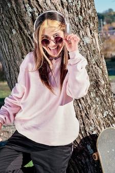 Piękna młoda kobieta w słuchawkach słuchanie muzyki stojącej na drzewie w różowym swetrze i duże okulary przeciwsłoneczne.