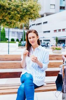 Piękna młoda kobieta w średnim wieku jedząca lody siedząca na ławce w parku