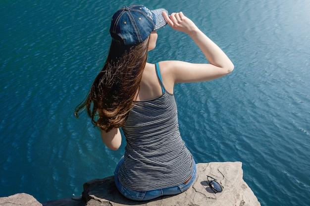 Piękna młoda kobieta w strój kąpielowy stojący nad jeziorem rano. turystyka koncepcyjna. koncepcja czasu letniego