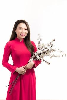 Piękna młoda kobieta w stroju azjatyckim (ao dai), trzymając kwiat, patrząc na kamery, uśmiechając się.