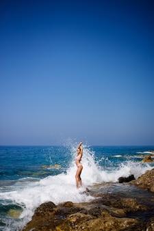Piękna młoda kobieta w stroju kąpielowym na kamienistej plaży w słoneczny dzień na tle fal. wakacje w sezonie letnim. selektywne skupienie