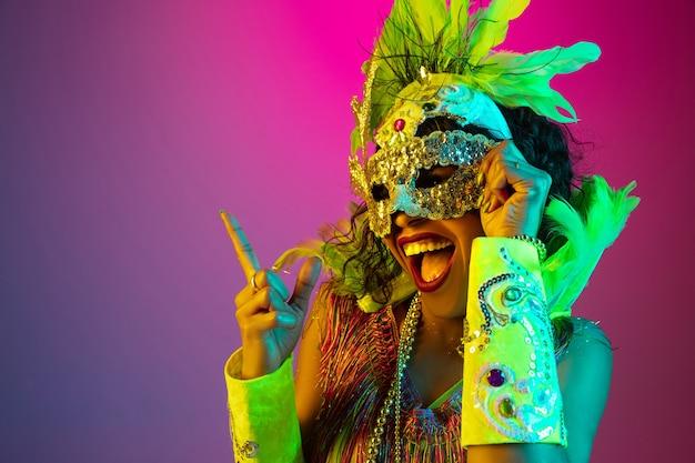 Piękna młoda kobieta w stroju karnawałowym i maskaradowym na gradientowym tle studia w świetle neonowym