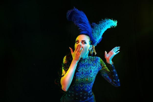 Piękna młoda kobieta w stroju karnawałowym i maskaradzie w kolorowe neony na czarnej ścianie