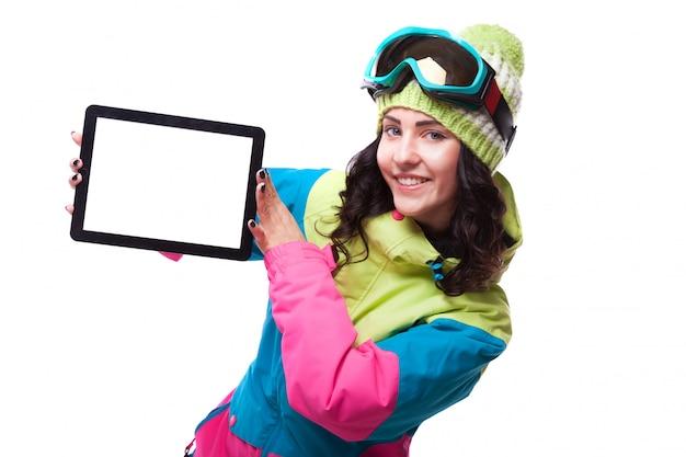 Piękna młoda kobieta w stroju narciarskim i gogle narciarskie trzymać pustą tabletkę