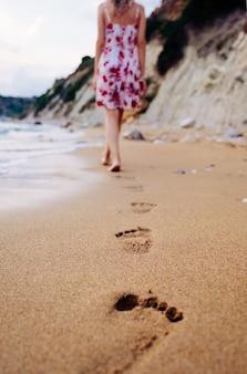 Piękna młoda kobieta w stylowej sukience spaceru boso po plaży, pozostawiając ślady na piasku o zachodzie słońca nad horyzontem.