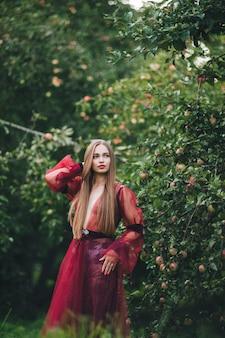 Piękna młoda kobieta w sukience barda patrzy na pole i ogród.