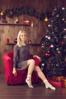 Piękna młoda kobieta w sukience, siedząc w czerwonym fotelu w noworocznym wnętrzu domu w pobliżu choinki. - obraz