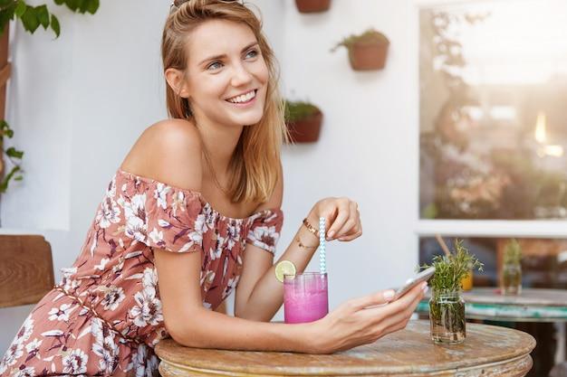 Piękna młoda kobieta w sukience w kawiarni