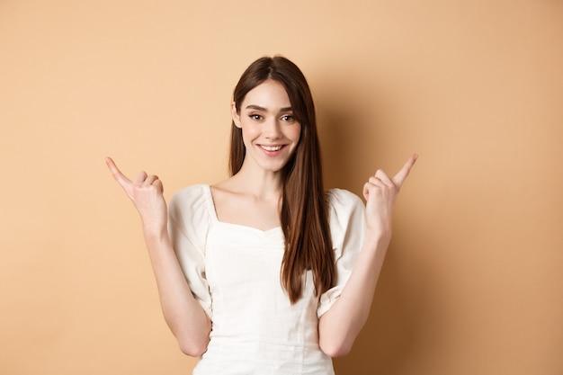 Piękna młoda kobieta w sukience, wskazując palcami na boki, pokazując dwa sposoby, dając wybór i uśmiechając się, stojąc na beżowym tle.