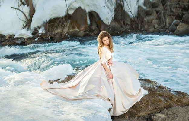 Piękna młoda kobieta w sukni ślubnej nad rzeką