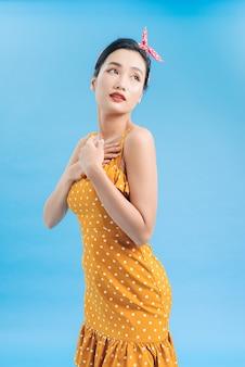 Piękna młoda kobieta w sukni trzyma ręce na klatce piersiowej, patrząc na kamery i uśmiechając się.