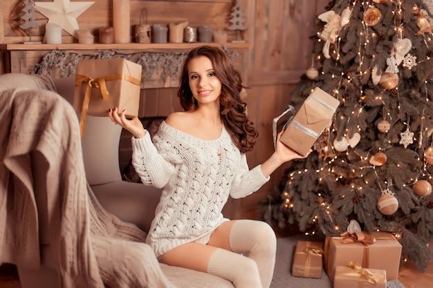 Piękna młoda kobieta w swetrze i pończochach siedzi w pobliżu pięknych choinek i trzyma w rękach prezenty, wnętrze nowego roku