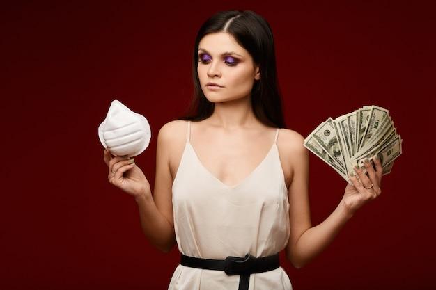 Piękna młoda kobieta w świetle sukni, trzymając maskę respiratora w jednej ręce i paczkę pieniędzy w drugiej. pojęcie kryzysu pandemicznego, epidemicznego i finansowego