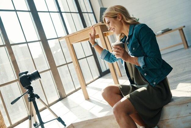 Piękna młoda kobieta w swobodnym ubraniu uśmiecha się i macha podczas pracy przed aparatem cyfrowym