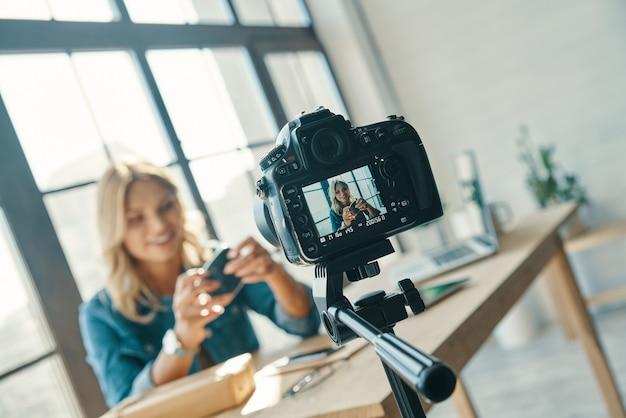 Piękna młoda kobieta w swobodnym ubraniu uśmiecha się podczas pracy przed aparatem cyfrowym