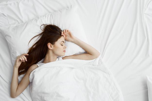 Piękna młoda kobieta w swoim pięknym śnieżnobiałym łóżku relaksuje i relaksuje