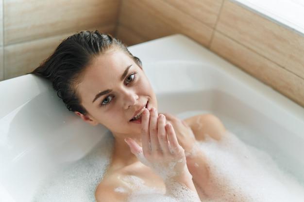 Piękna młoda kobieta w swojej pięknej śnieżnobiałej wannie odpoczywa i relaksuje, piękny dowód, wanna z pianką