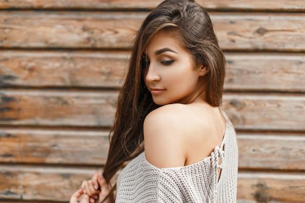 Piękna młoda kobieta w szarym swetrze w pobliżu vintage drewnianej ścianie