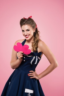 Piękna młoda kobieta w ubrania w stylu pin-up, trzymając kształty serca