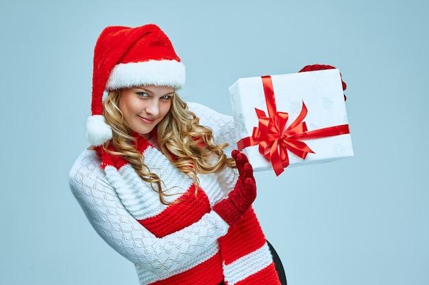 Piękna młoda kobieta w ubraniach świętego mikołaja z prezentem na szarym tle