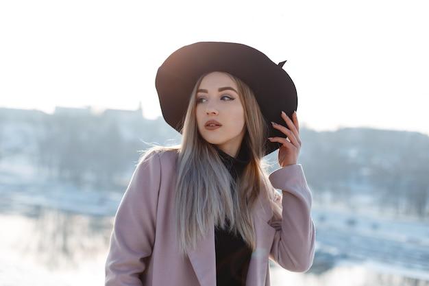 Piękna młoda kobieta w vintage elegancki czarny kapelusz w ciepłym różowym płaszczu w golfa z dzianiny pozuje na tle zimowej rzeki. modna blondynka. kobieca moda.