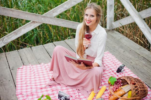 Piękna młoda kobieta w vintage ubrania ma piknik na drewnianym molo sam. piknik w stylu francuskim na świeżym powietrzu