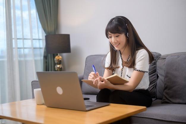 Piękna młoda kobieta w zestawie słuchawkowym prowadzi wideokonferencję za pomocą komputera w domu