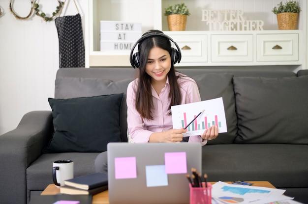 Piękna młoda kobieta w zestawie słuchawkowym prowadzi wideokonferencję za pośrednictwem komputera w domu podczas pandemii koronawirusa