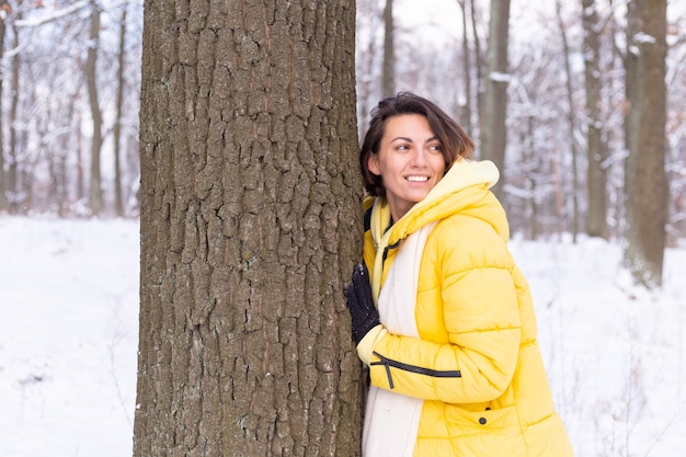 Piękna młoda kobieta w zimowym lesie okazuje czułe uczucia do natury, pokazuje swoją miłość do drzewa