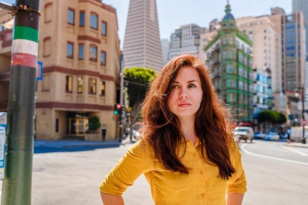 Piękna młoda kobieta w żółtej koszuli w centrum biznesowym z widokiem na wieżę transamerica