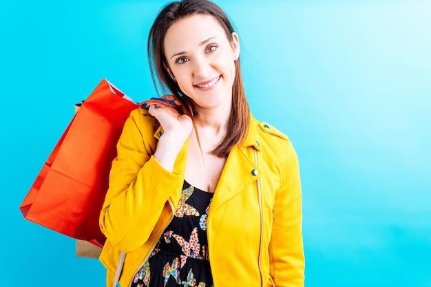 Piękna młoda kobieta w żółtej kurtce na niebieskim tle trzymając kolorowe torby na zakupy. ona zakupoholiczka koncepcja. weekend na zakupy. wyprzedaż
