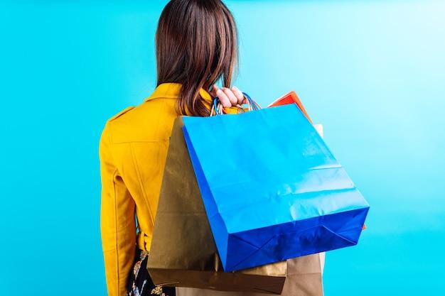 Piękna młoda kobieta w żółtej kurtce na niebieskim tle trzymając kolorowe torby na zakupy przyklejanie na plecach. ona zakupoholiczka koncepcja. weekend na zakupy. zmniejszenie