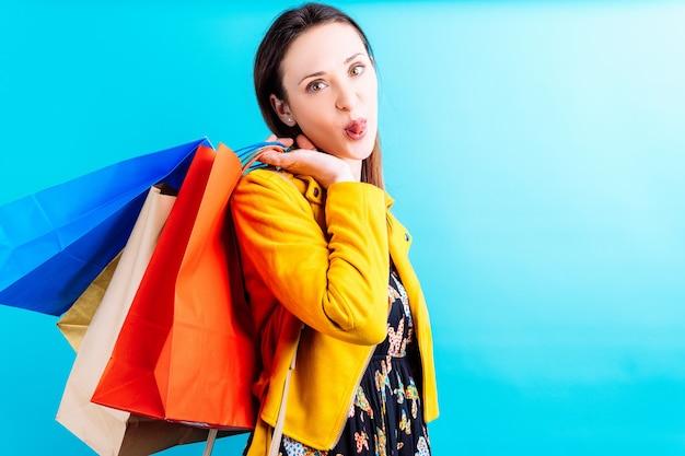 Piękna młoda kobieta w żółtej kurtce na niebieskim tle trzymając kolorowe torby na zakupy wystaje jej język. ona zakupoholiczka koncepcja. weekend na zakupy. wyprzedaż