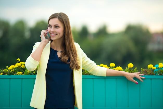 Piękna młoda kobieta w żółtej kurtce rozmawia przez telefon latem