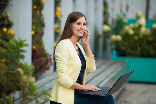 Piękna młoda kobieta w żółtej kurtce z laptopem w letnim parku