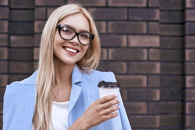 Piękna młoda kobieta w zwykłych ubraniach i okularach trzyma filiżankę kawy i