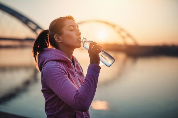 Piękna młoda kobieta wody pitnej jogger po ciężkim treningu na świeżym powietrzu.