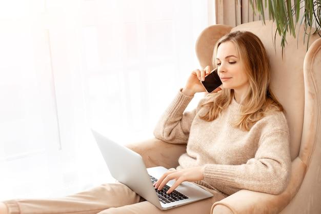 Piękna młoda kobieta, wpisując na laptopie i telefon, siedząc na krześle w pobliżu okna. koncepcja pracy w biurze domowym, zakupy online, praca freelancera, informacje o surfowaniu po sieci, koncepcja technologii