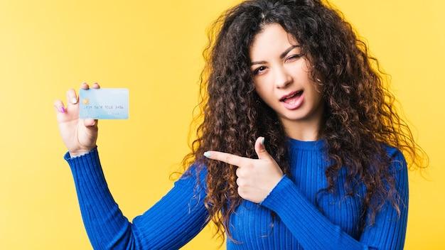 Piękna młoda kobieta wskazując na kartę debetową. transakcja bezgotówkowa elektroniczna metoda płatności e-commerce.